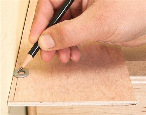 Cheap scribe's tool. Mark a scribe line on the board using a pencil and a small washer. The washer follows any bumps or curves in the wall.