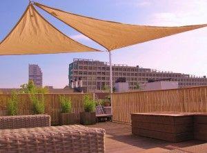 Hardhouten dakterras met een hekwerk bekleed met bamboe en een zonnezeil in Zeeburg in Amsterdam.
