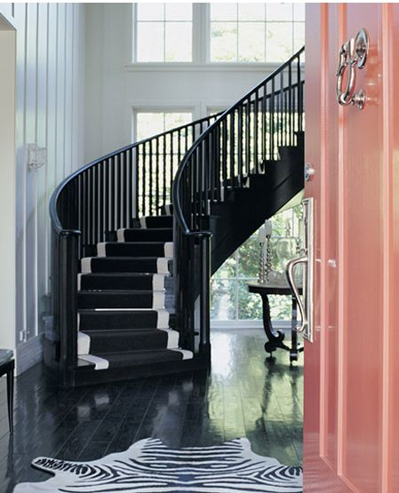 black staircase + pink front door + zebra rug in entryway