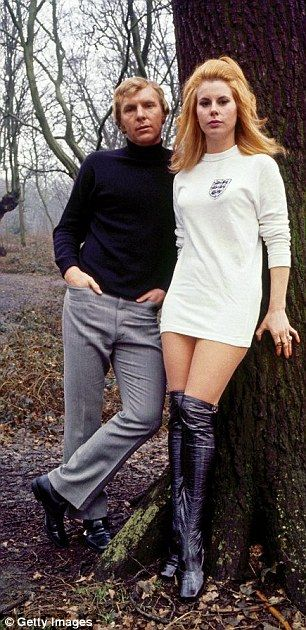 England football captain Bobby Moore (1941-1993) with Tina, wearing an England shirt, 1972...