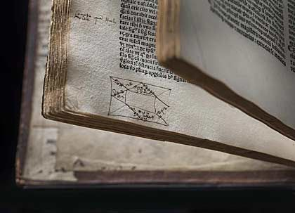 a photo of the open pages of a book with a small rectangular doodle at the bottom of the page