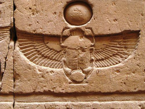 O Sol Nascente, representado por Khepri sob a forma de um escaravelho com as asas de Ísis, empurra o disco solar.