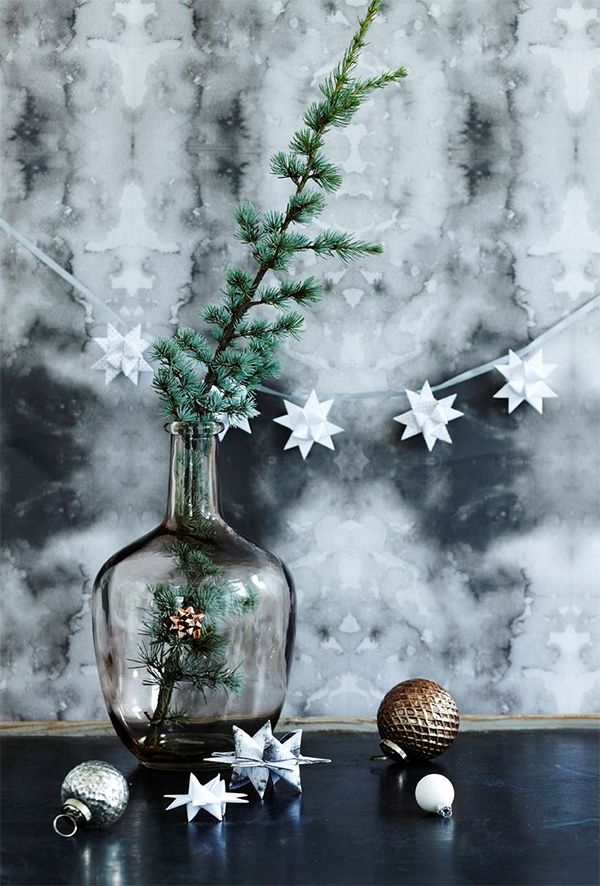 Little Swedish Christmas stars and a pine bough in a dark glass bottle