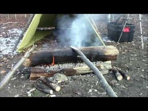 ▶ Make A Campfire Last All Night - YouTube  Summary: Traditional Scandanavian fire method that radiates heat out and down instead of up.  Find/make 2 logs that are an inch thick per hour of burning time and 3 feet per person consuming the fire. Dead standing trees (identified by sections without bark) are best; dead fallen trees off the ground are second best. Stack one on top of the other 3-3.5 ft from shelter.
