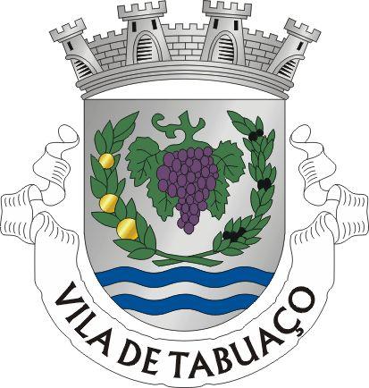 """Civic heraldry of Portugal - Brasões dos municípios Portugueses. BRASÃO: Escudo de prata com um cacho de uvas de púrpura folhado e troncado de verde, cercado por dois ramos unidos em círculo, um de laranjeira frutado de ouro e outro de oliveira frutado de negro, ambos folhados de verde. Em contra-chefe, duas faixas onduladas de azul. Coroa mural de quatro torres de prata. Listel branco com os dizeres: """" VILA DE TABUAÇO """", a negro."""