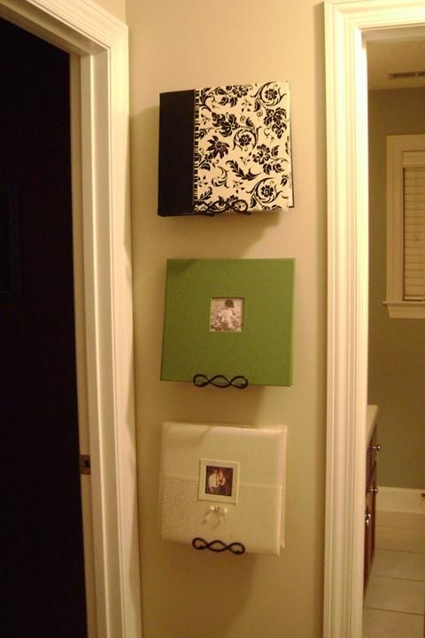 Photo albums displayed on plate hangers! This is genius! Would be great for cookbooks too!