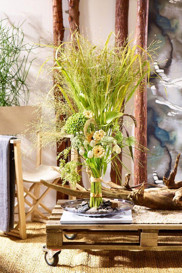 """Du bist natürlich und ungezähmt?  Dann ist der """"Eco Booster"""" das richtige für Dich. Dieser hochgebundene Gras-Strauß macht sich hervorragend im urbanen Dschungel. Auf einer schlichten Glasschale kommt er besonders zur Geltung. Toughe raue Materialien wie Holz, Stein, Leinen, Baumwolle, Sisal und recyceltes Mobiliar sind die perfekten Begleiter für den """"Eco Booster"""". Ein energievoller Mix aus Gräsern und Blüten im Frühling 2017."""