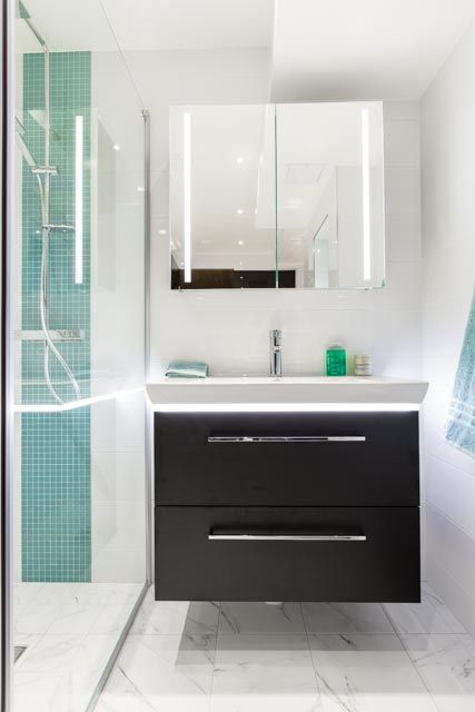 Ett toppmodern badrum i vitt och svart med inslag av turkos mosaik. Duschutrymmet utgörs av en vägg och en dörr i glas. Handfat och toalett är vägghängda och går i färg med det stora svarta badkaret. Bakom en vägg i mörkt glas döljer sig en bastu i två plan med ett modernt bastuaggregat.