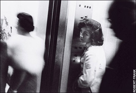 """Robert Frank, Elevator - Miami Beach. """"And I say: That little elevator girl looking up sighing in an elevator full of blurred demons, what's her name & address?"""" - Jack Kerouac, Introduction, The Americans."""