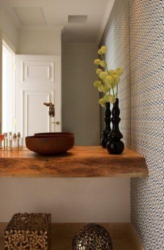Em contraponto ao revestimento de parede com desenho gráfico; a bancada de tora, a torneira caipira e a cuba aço com aspecto enferrujado, remetem a um lavabo rústico. O projeto é do escritório Messa Penna.