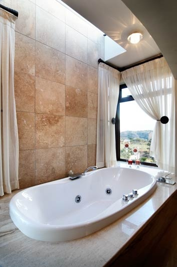 Stately #travertine #marble has been used on the walls, with marble slabs for the #bath surround, creating a perfect space for relaxation. #UnionTiles