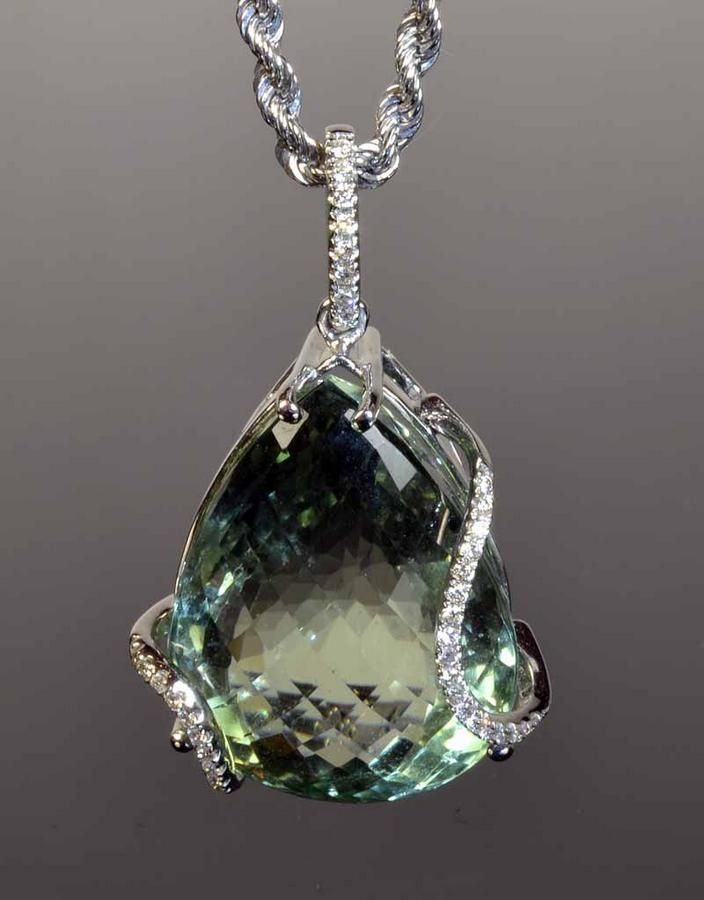 18ct white gold prasiolite and diamond pendant. The valuation states the pear shaped chequerboard cut, mint green prasiolite measures 22 x 16 x 13mm. The setting features two curved diamond set bands and a diamond set bale, with an 18ct white gold chain, stamped 750 Italy