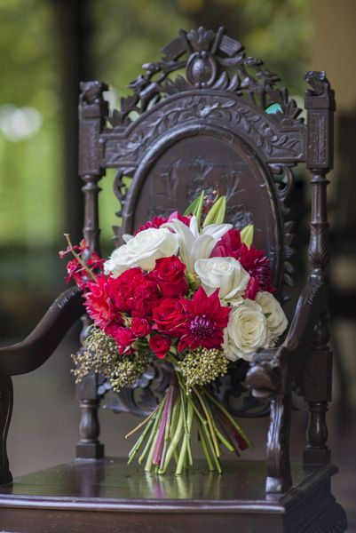 A lovely bouquet of deep cadmium red, and rich creamy blooms showcasing one of our beautifully carved chairs from the Orangery verandah