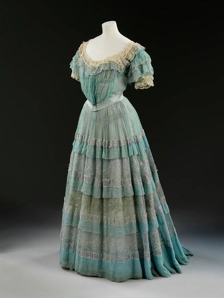 1905, England  'Carresaute' evening dress by Lucile  Silk chiffon over silk linings, boning, metallic embroidery, lace, ribbon flowers, self fabric ruffles and frills  V Museum