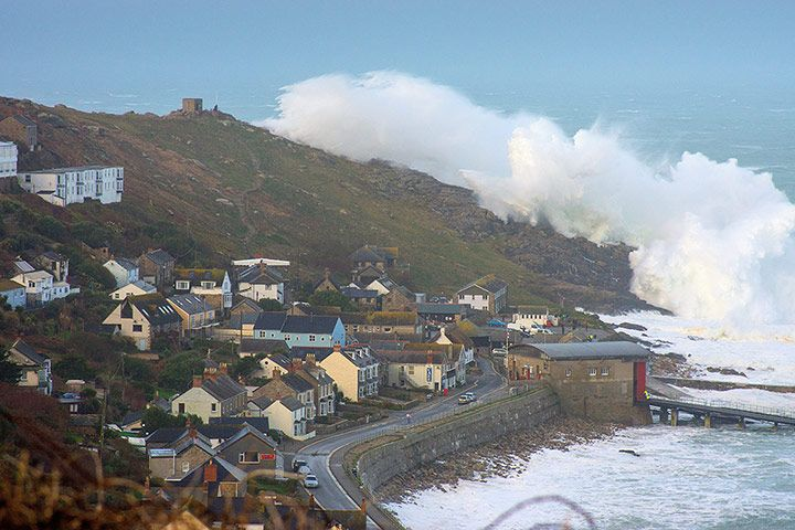 Credit: Roger Sharp/SWNS A massive plume of spray arches over a group of houses near Sennen Cove, Cornwall.