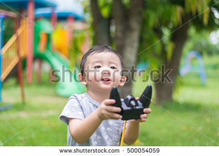 Little Asian kid holding a radio remote control (controlling handset) for helicopter , drone or plane at the playground, school yard. Happy kid in kindergarten or preschool.shallow DOF