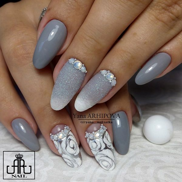 Gray themed rose nail art design. The roses are in white polish as they are surrounded by embellishments on each nail. The nails also sport a gradient gray to white glitter gradient effect.
