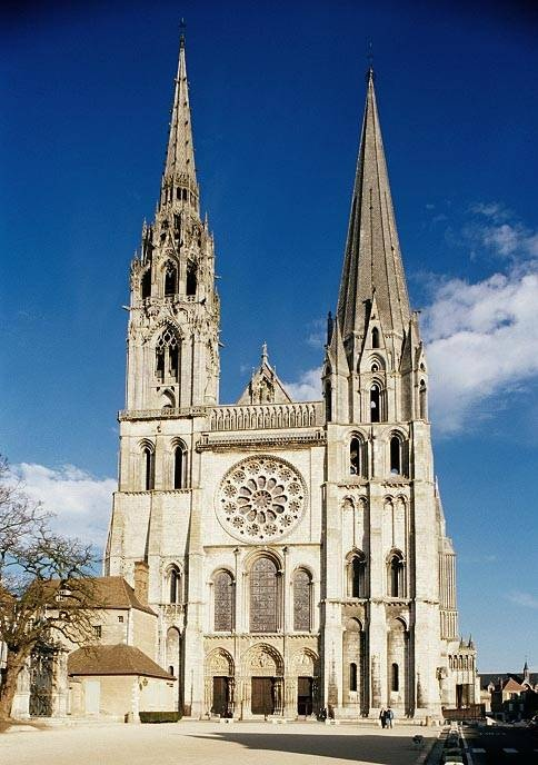 This is the Chartres Cathedral in Chartres France that was rebuilt in  the 13th century after majority of the building was destroyed by fire in 1194. The church is designed with pointed arches, ribbed vaulting, large stained glass windows, and constructed from limestone.