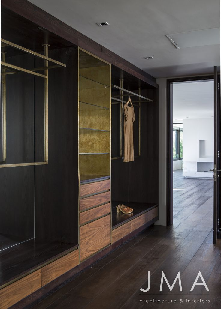 A beautiful open plan closet with brushed gold inserts contrasted against dark wood.