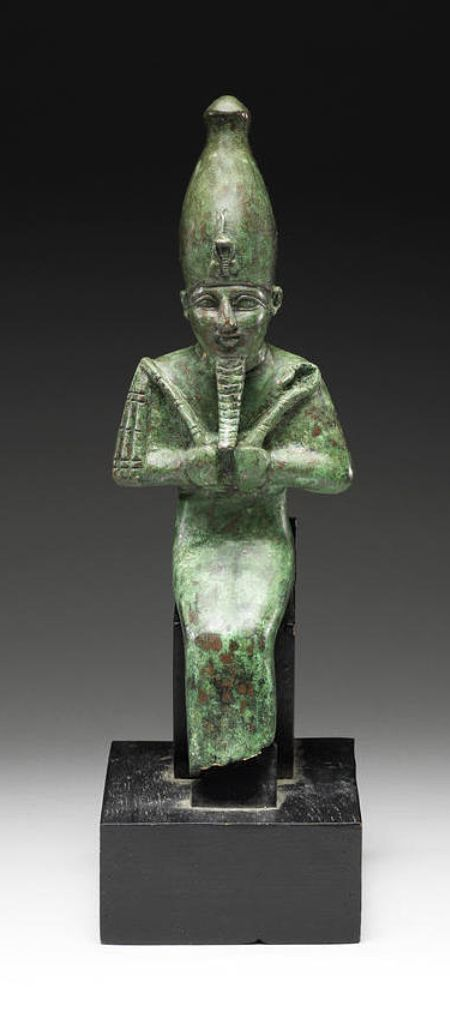 An ancient Egyptian bronze seated figure of Osiris, god of the underworld, depicted mummiform, with his symbolic attributes of the crook and the flail, and wearing the white crown (symbol of Upper Egypt) with uraeus (a symbol of divine protection) and long false beard (a symbol of divinity). (Bonham's)