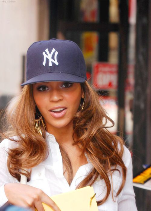 Love this look. Of course you would wear big hair a new York Yankees cap with a crisp white shirt! I'm guessing she's got jeans and heels on too. Go Bey!