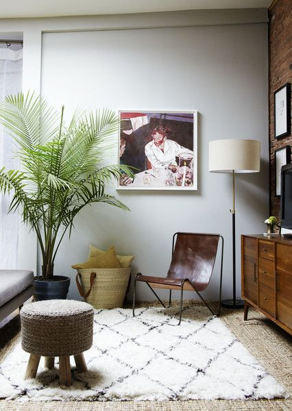 This corner features a media console and cozy additions like a shag rug, ottoman, and chair.