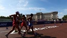 Athletes walk past Buckingham Palace