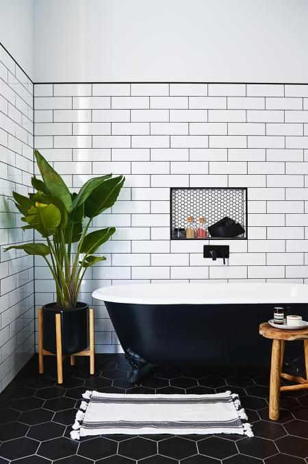 Black and white bathroom, black bath tub white subway tiles and large plant