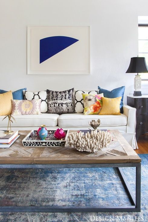 Always love the mismatched smattering of colorful pillows on a white sofa. Plus love the faded old looking rug