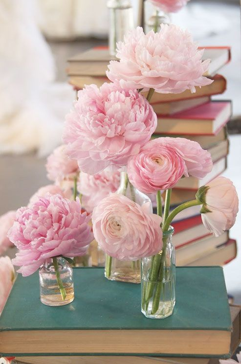 A mixture of pink peonies and pink ranunculus fill vases in varying heights.