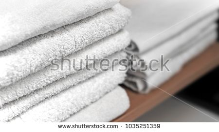 Folded white towels stacked on a shelf.