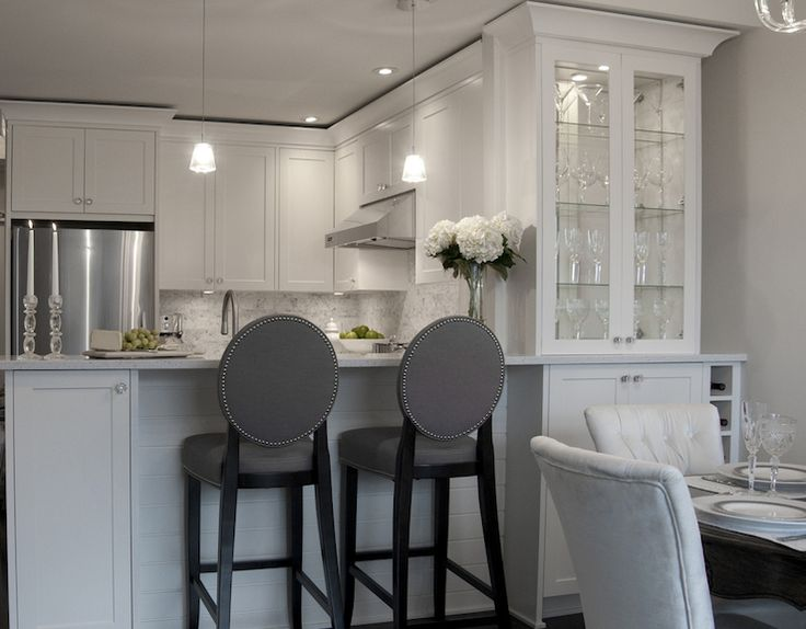 kitchens - white silk tufted dining chairs gray linen oval back chic counter stools bredakfast bar built-in wine rack glass-front hutch white shaker kitchen cabinets granite counter tops white carrara marble subway tiles backsplash