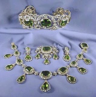 The Habsburg Peridot Parure A complete parure of peridot jewels: a tiara, a necklace, earrings, and substantial brooch. c. 1820s attributed to Köchert, who later become imperial court jewelers to the Habsburgs. Large diamond scrolls, the center of which are studded with absolutely enormous peridots. The tiara can also be supplemented with seven of the pendants from the necklace, which can be set upright atop the piece. A delicate floral motif runs through all of the pieces in the parure.