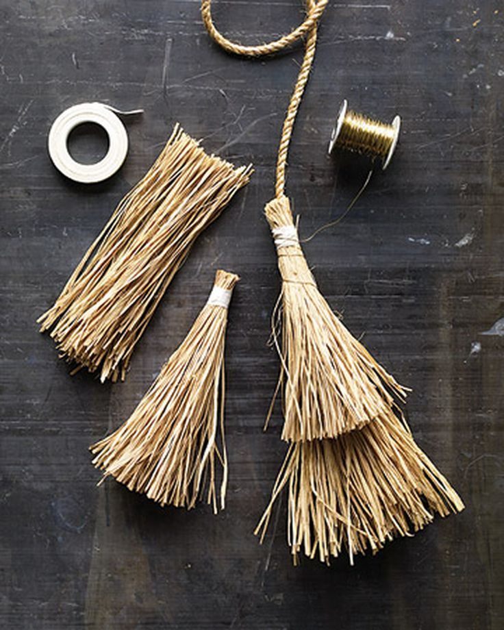 Two brooms wired together form an unwelcoming decoration on the witch's front door, which also has a border of little broom heads (bundles of raffia).