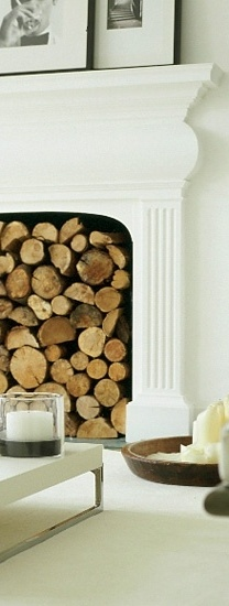 Beautiful white fireplace & white decor in striking contrast to the warm wood in the fireplace -
