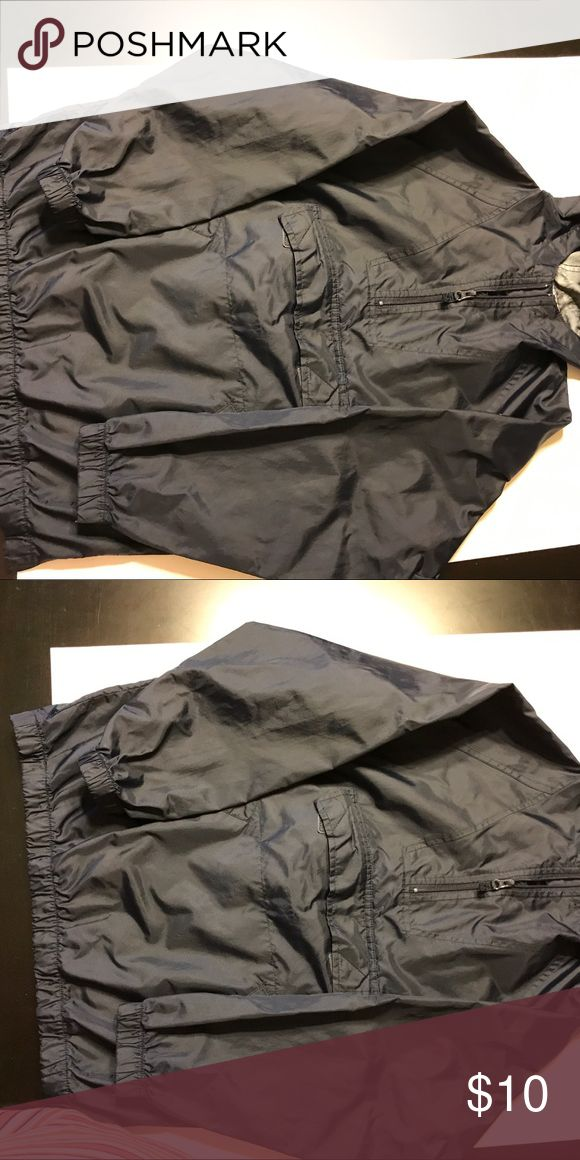 """Boy's anarak rain jacket size S/M Gap 20"""" under arms across and 22"""" length. Blue camo pattern across back yoke, elastic at waist and cuffs, hooded. Perfect condition. Ventilation gussets.under arms, side and1/4 neck zip. Name in gray letters at neck.Pictures show two size 8 shirts on top of the jacket. GAP Jackets & Coats Raincoats"""