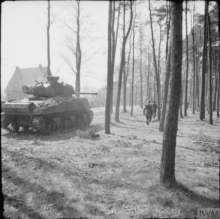 A Sherman Firefly of 5th Canadian Armoured Division assists troops of 11th Royal Scots Fusiliers to clear the Germans from Ede, 17 April 1945.