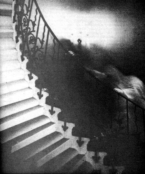 "Rev. Ralph Hardy, a retired clergyman from White Rock, British Columbia, took this now-famous photograph in 1966. He intended merely to photograph the elegant spiral staircase (known as the ""Tulip Staircase"") in the Queen's House section of the National Maritime Museum in Greenwich, England. Upon development, however, the photo revealed a shrouded figure climbing the stairs, seeming to hold the railing with both hands,"