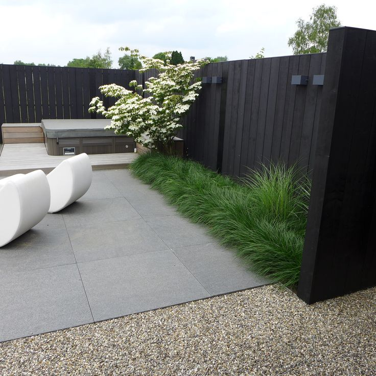 Modern garden with dark toned fence.                                                                                                                                                                                 More