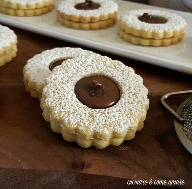 Gli occhi di bue con crema alle nocciole, solo dei golosissimi e friabilissimi biscotti realizzati con pasta frolla e ripieni di crema alle nocciole.