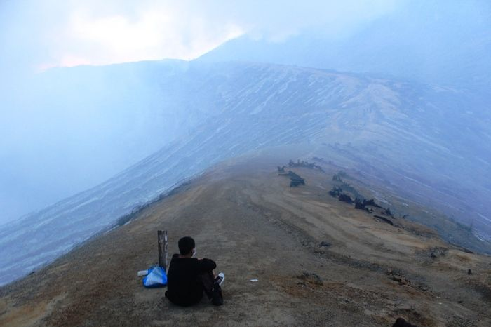 Sulfur screen: A traveler sit in front of a sulfuric fog that barred the path leading to the Mount Ijen's crater. A trekker often waits until the heavy smoke gone. (Photo by Hanna Nabila).