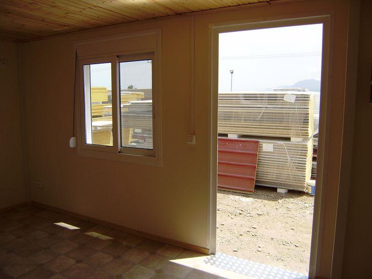 Λεπτομέρεια από το εσωτερικό του living room ενός οικίσκου. Βλέπετε και την κυρία είσοδο που η πόρτα της είναι ανοιχτή.