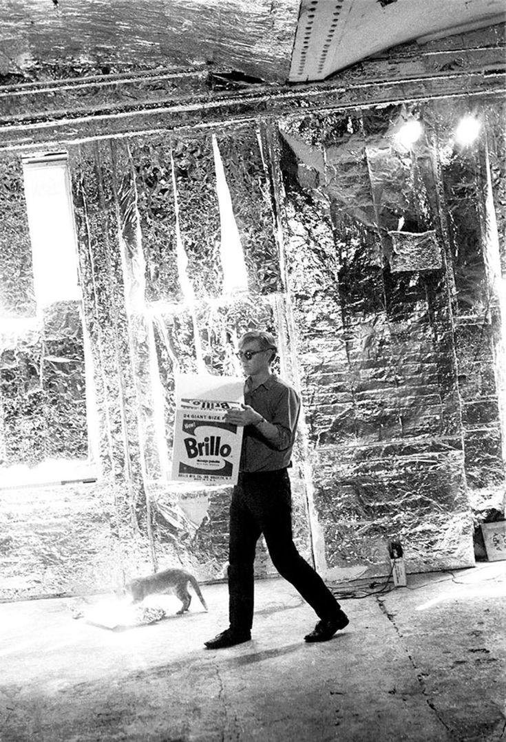 1964: Andy Warhol carrying a Brillo Box sculpture with Billy Name's cat Ruby at the Factory