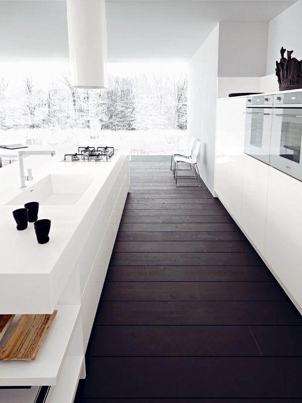 Contrast of dark wooden floors and modern white interior. Beautiful kitchen and the winter scenery outside is perfect!