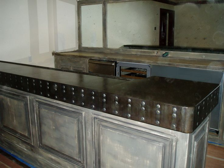 The dark patina and contrasting decorative rivets gives this zinc bar top a bold, masculine statement. Love it