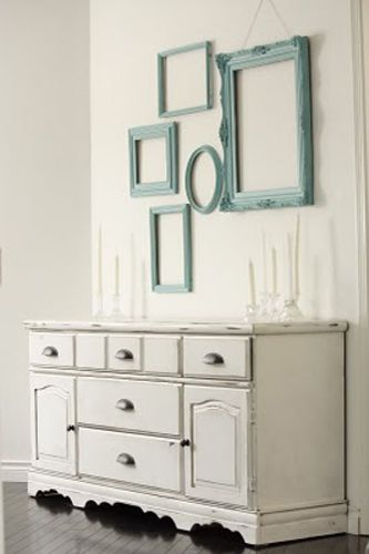 empty picture frames in various sizes and styles in blue color on the white wall