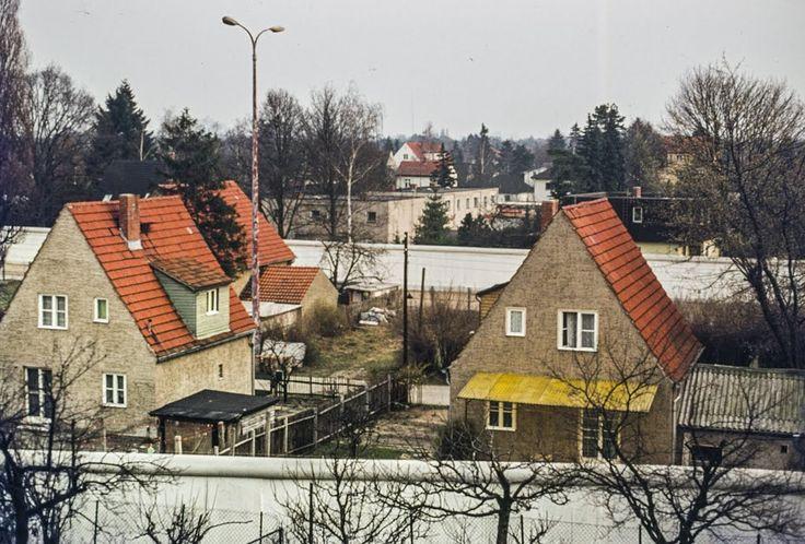 """1986 West-Berlin - Berliner Mauer, Blick auf den Entenschnabel (Brandenburg). Die schmale Stichstraße """"Am Sandkrug"""" ist hinter den vorderen Häusern zu sehen. Das Bild entstand vom Grundstück """"Am Rosenanger 50"""" und zeigt den Mauerverlauf von der Frohnauer Seite und hinten von der Hermsdorfer Seite. Ein gerade vorbei fahrender Bus der BVG fährt auf der Burgfrauenstaße, die wieder im Westteil der Stadt liegt. Das Bild zeigt den Zustand der Mauer aus der """"4. Generation"""", die um 1980 erneuert…"""