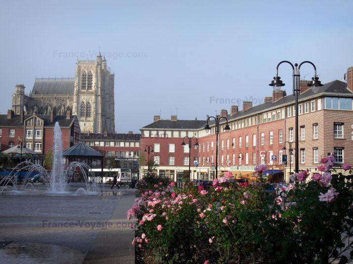 Abbeville: St. Vulfran collegiale gotische stijl, plein met een scheutje water en rose (roze), straatverlichting en gebouwen in de stad - France-Voyage.com