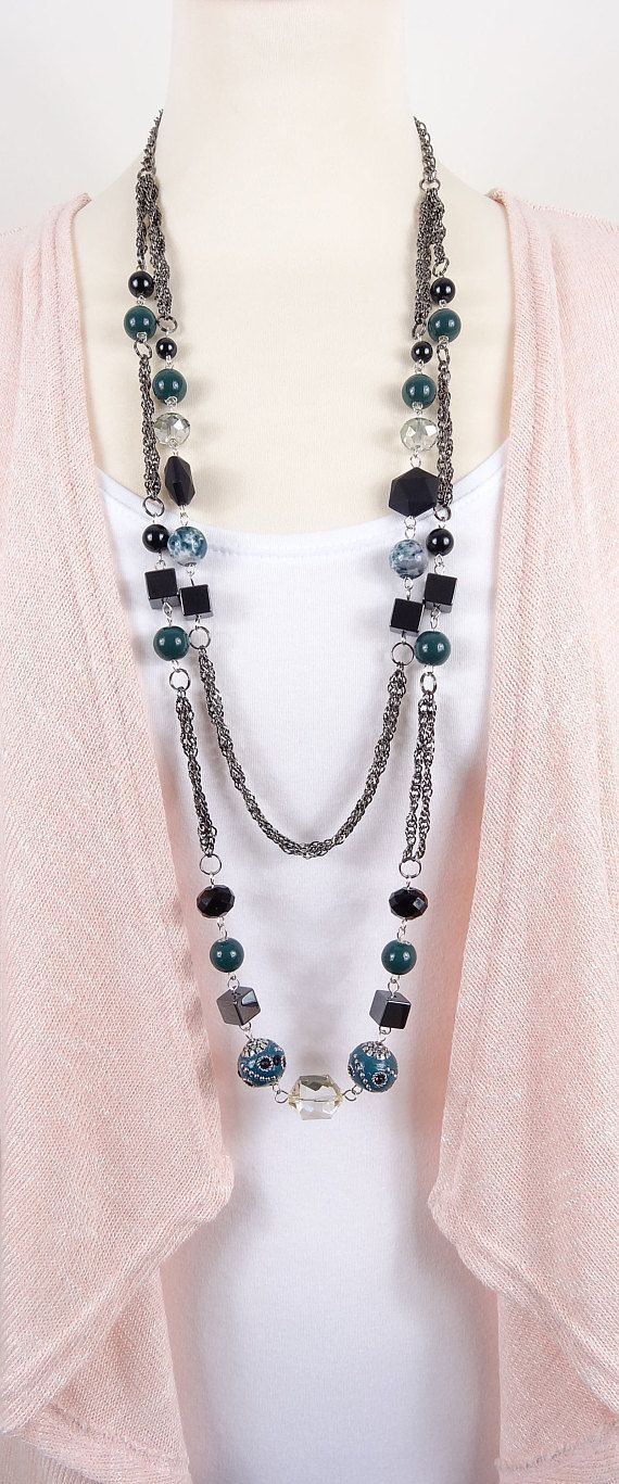 Varied shades of dark green/teal green and black beads and gunmetal plated jewellery chain, make up this long necklace. I have used glass pearls, ceramic beads, acrylic beads and hematite beads which lends interest and texture to this piece. The necklace is 38 inches/96 cms long,