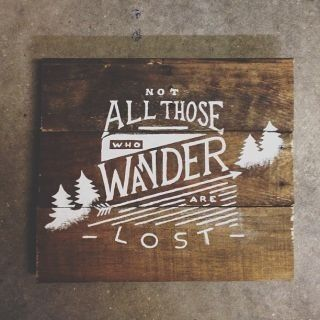 Wood texture?White text/graphics? Not all those who wander are lost. Wooden sign.